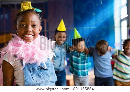 Portrait of girl wearing feather boa with friends in background during birthday party