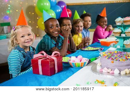 Portrait of children sitting at table during birthday party