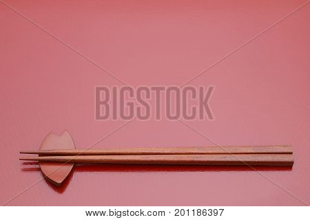 Chopsticks and chopsticks rest on red table background