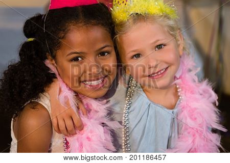 Portrait of smiling girls with arm around wearing feather boa