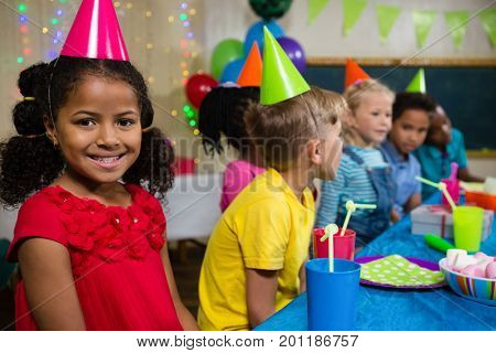 Portrait of smiling girl sitting with friends at table during birthday party