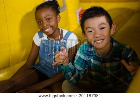 Portrait of happy girl and boy sitting on bouncy castle