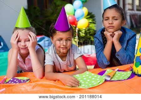 Bored children sitting at table during bithday in yard