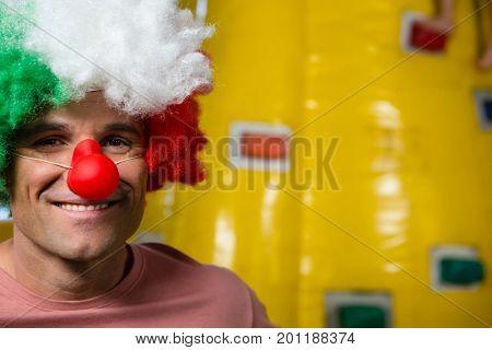 Portrait of man wearing clown nose against bouncy castle