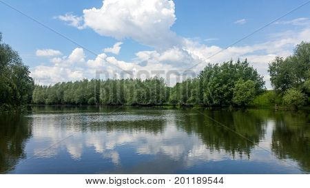 Forest lake under blue cloudy sky. blue cloudy sky