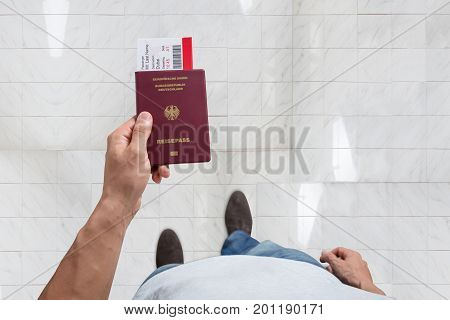 Elevated View Of Male's Hand Holding Passport And Boarding Pass Standing On Floor