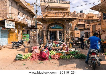 JAISALMER RAJASTHAN INDIA - MARCH 07 2016: Wide angle picture of indian people selling vegetables at the street market in Jaisalmer known as Golden City in India.