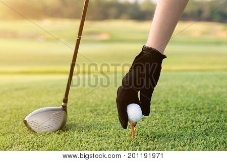 Hand placing a tee with golf ball. Hand hold golf ball with tee on course close-up