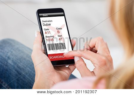 Cropped image of woman generating boarding pass on smart phone at home