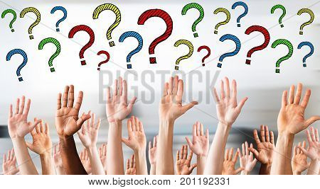 Digital composite image of multicolored question marks above business people's hands