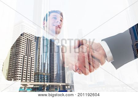 Low angle view of young businessman shaking hand with coworker over city background