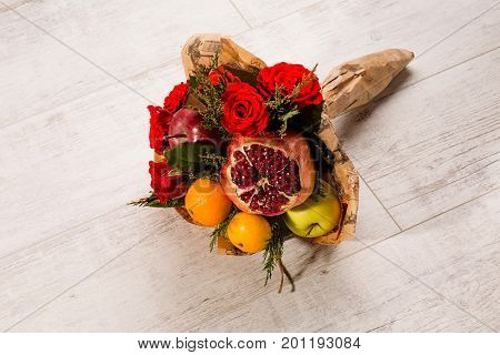 Unusual presents concept. Prettily wrapped composition of red roses and fruits.
