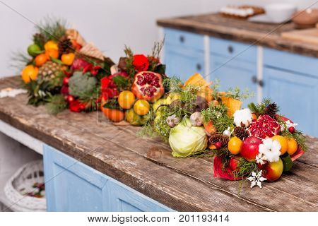 Nice original bouquets of edible fruits and vegetables. Eatable composition on wooden desk in the kitchen.