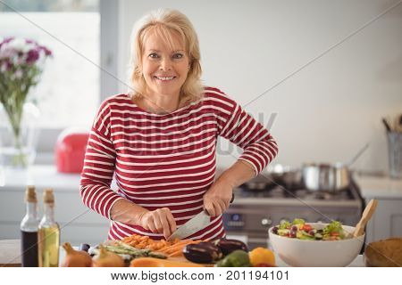 Portrait of senior woman chopping vegetables at home