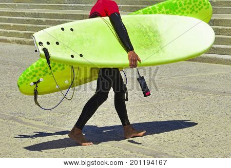 Surfer in wet suit after training and in hands holds surfboards. Teacher in a serf school