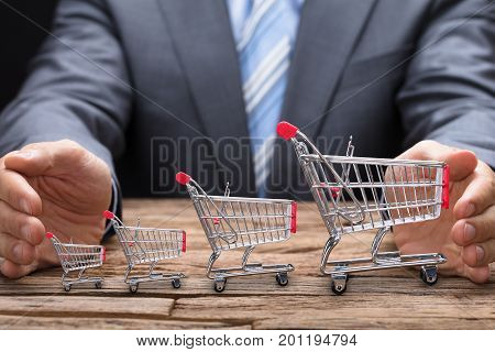 Midsection of businessman covering various shopping carts on wooden table