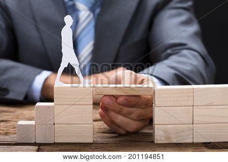 Midsection of businessman placing hand between wooden blocks with paperman walking on it