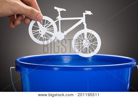 Cropped hand of businessman throwing paper bicycle in blue bucket against gray background