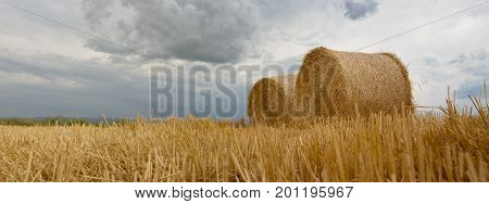 Straw bales on farmland Storm clouds. Straw bales on farmland