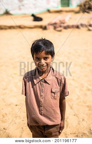 RAJASTHAN INDIA - MARCH 07 2016: Vertical picture of native indian boy smiling in Thar Desert located close to Jaisalmer the Golden City in India.