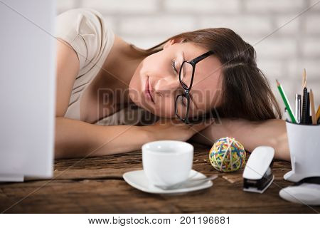 Young Businesswoman Wearing Eyeglasses Napping In Office