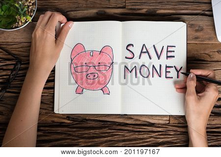 Elevated View Of A Businessperson Drawing Save Money Concept On Notebook