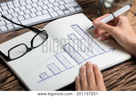 Close-up Of A Businessperson's Hand Drawing Graph With Pen On Notebook