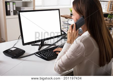 Businesswoman Talking On Landline Phone With Blank White Computer Screen On Desk