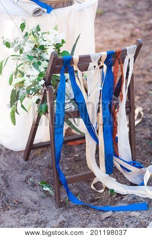 Decorative red, blue and white ribbons on chair. Decorated chairs with red bows in a row. Silk bow tied on back of chair in party at wedding.