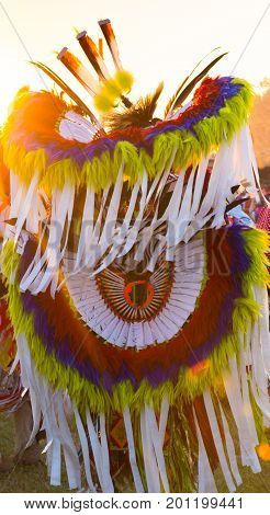 A brilliantly colored garment worn at a Pow Wow with feathers in blue red yellow and white. Photographed with the setting sun in the background. Shallow depth of field.