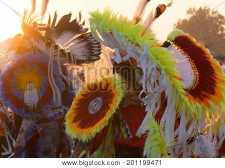 A riot of color in the headdresses worn at a Pow Wow. Feathers ribbons and beads in red yellow orange blue and white are photographed with a shallow depth of field and back little by the setting sun.