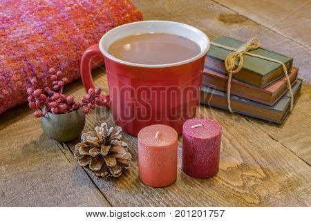 Warm red mug of hot chocolate on rustic wooden table cozy autumn blanket and fall candles vintage books pinecone and berries