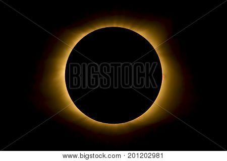The moon covers the sun and displays the star's corona and some red prominences during totality. Photographed near Cerulean Kentucky during the Total Eclipse of August 21 2017.