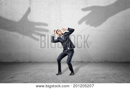 A scared businessman hides from two giant shadows of human hands reaching to him. Fear of unknown. Unreliable partnership. New business venture.