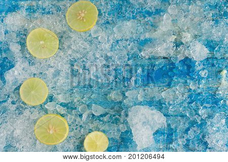 Crushed Ice Cubes And Lemon, On Vintage Blue Wooden Table. Top View