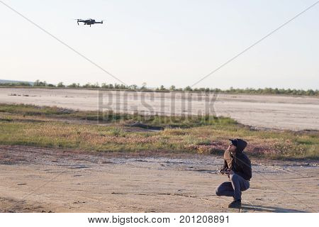 picture of black flaying quadrocopter dron and pilot siluette in sunset light background, tourist use dron helicopter to photography or filming desert landscapes
