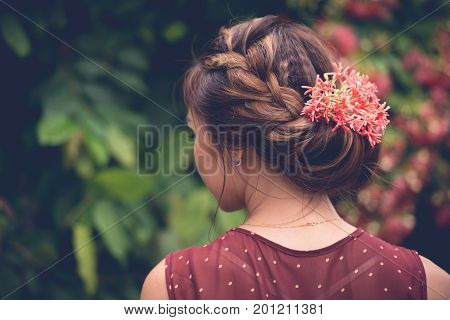 Young woman with summer updo. Simple hairstyle with flowers