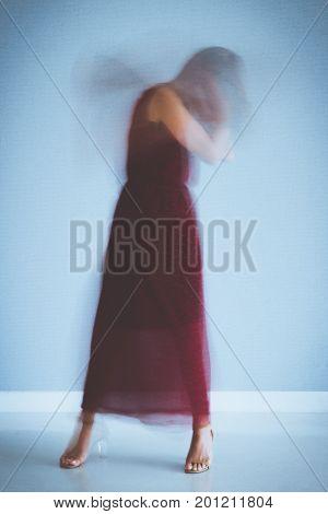 Blurred motion of young woman enjoying dancing