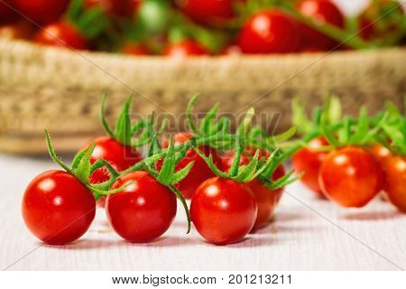 Fresh cherry tomato on wood basket. Close up lovely cherry tomato for background or wallpaper. Prepare fresh cherry tomato for home cooking look so delicious. Side view selective focus on foreground. Cherry tomato in fresh vegetable concept