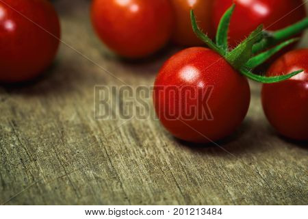 Fresh cherry tomato on rustic wood table. Close up lovely cherry tomato for background or wallpaper. Prepare fresh cherry tomato for home cooking look so delicious. Macro concept with copy space. Cherry tomato in fresh vegetable concept.