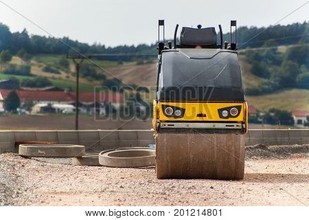 Road roller working on the new road construction site. Construction machine on an empty construction site