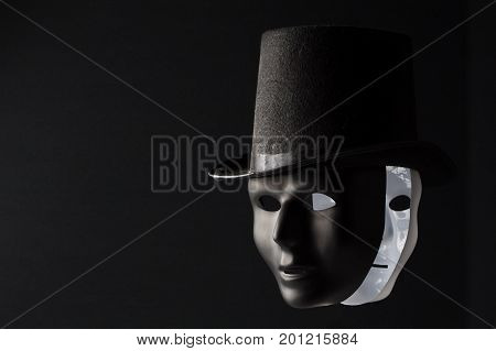 Black and white masks wearing black top hat isolated on black background with copy space. Hypocricy and double game concept
