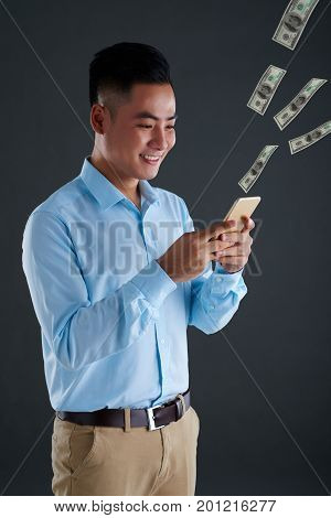 Smiling Asian man spending money when using application on smartphone
