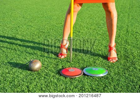 girl with high-heeled shoes and athletic gear discus javelin and hammer