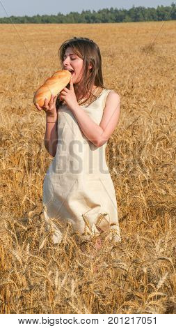 Pretty Girl in the field bites a loaf of bread