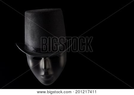 Black mask face wearing black top hat isolated on black background with copy space
