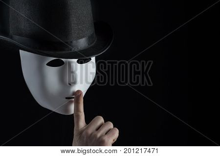 Male finger showing shh sign on white mask wearing black top hat on black background with copy space. Freedom of speech and silence concept