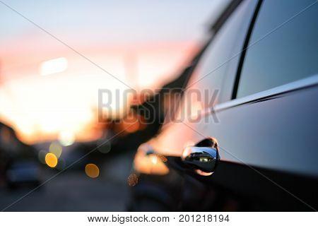 Luxury Vehicle Black Car With Blur Twilight Dramatic Sky, Image Selective Focus On Door Handle