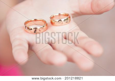 Two wedding rings lie on an open palm