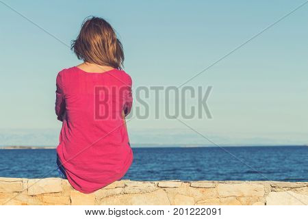 Lonesome girl sitting on the coast and watching the sea / ocean. poster